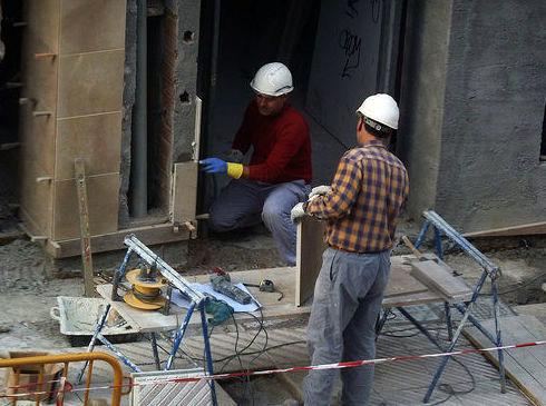 Imagen de dos obreros con casco blanco trabajando en la calle